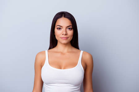 Portrait of a young latino american mulatto girl. She is in a casual white singlet standing on the pure light blue background 스톡 콘텐츠