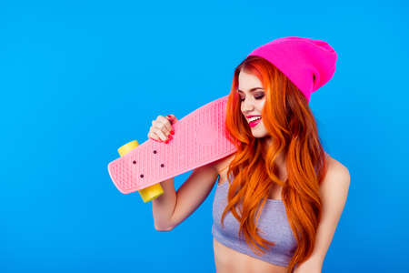 Girl with long board. More colors to your life! Foxy cute charming model in hat and with skate board on blue background. Ginger is so attractive and colorful Reklamní fotografie