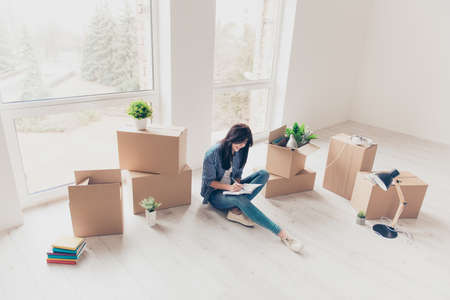 Home, sweet home! Young girl in casual clothes is sitting with crossed legs on the floor of her new apartment. She just moved in, writing about her feelings in diary. A lot of unpacked boxes near her Stock Photo