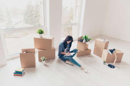 Trautes Heim, Glück allein! Junges Mädchen in ungezwungener Kleidung sitzt mit gekreuzten Beinen auf dem Boden ihrer neuen Wohnung. Sie ist gerade eingezogen und hat über ihre Gefühle im Tagebuch geschrieben. Viele ausgepackte Kartons in ihrer Nähe Standard-Bild