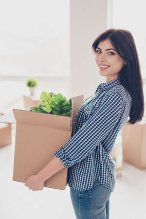 Successful young woman is moving to new nice place and holding box with her belongings. The room is very light and bright, she is wearing cassual outfit