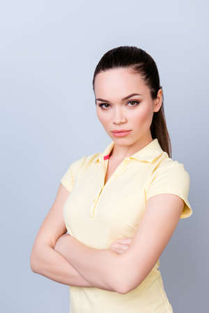 pedant: Portrait of serious young freelancer brunette lady, she stands with crossed hands in yellow tshirt on pure light background. So severe and strict Stock Photo
