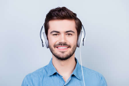 Happy young cute guy is listening to the music in big white headphones on light blue backgroung