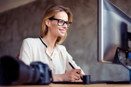 Smiling happy woman in glasses sitting at the table in front of computer screen and retouching new photos