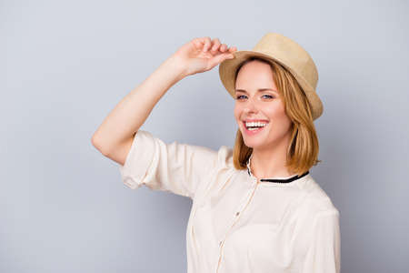 Summer is here! Young cute smiling blond lady in hat at the light grey background. She is happy, wearing casual beige shirt Stock Photo