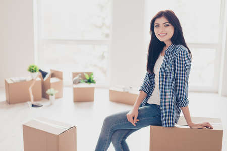 Home, sweet home! Young cute girl in casual clothes is sitting on the box with her belongings in the new light modern apartment. She just moved in, A lot of unpacked boxes near her Фото со стока