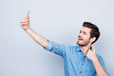 Cheerful young man is making selfie on the camera of his phone and showing thumb up, smiling