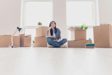 Low-Winkel-Foto von brunette junge Frau in helle moderne Wohnung, nach oben und träumen, planen, wie sie den Raum in neue Wohnung zu organisieren Standard-Bild - 84075383