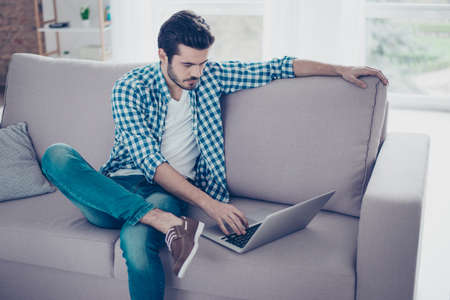 Young freelancer sitting on couch at home and using laptop for his work Фото со стока