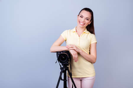 beaming: Cheerful female photographer is standing near the camera in casual clothes on the pure background. She has a beaming smile