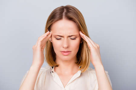 Too much work! Close up of depressed young blond woman with terrible headache touching temples with fingers on pure light background Stok Fotoğraf