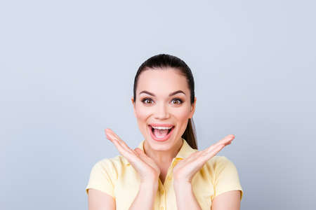 De ninguna manera! ¡¿De Verdad?! Chocante joven atractiva chica es la celebración de sus palmas cerca de su cara. Ella está emocionado y con la boca abierta sobre fondo de luz pura, que está llevando camiseta casual de color amarillo Foto de archivo - 84075626