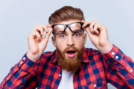Its incredible! Close up portrait of young bearded man touching the spectacles and keeping his mouth open against gray background