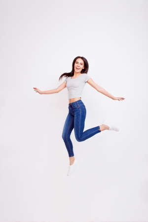 Dream big! Cheerful girl is jumping and feel so carefree and happy on pure white background wearing casual outfit