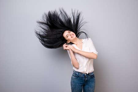 目を閉じて幸せはカジュアルな服装で夢のようなブルネットは、彼女の髪が宙を舞う、彼女は純粋な灰色の背景の上に立つ
