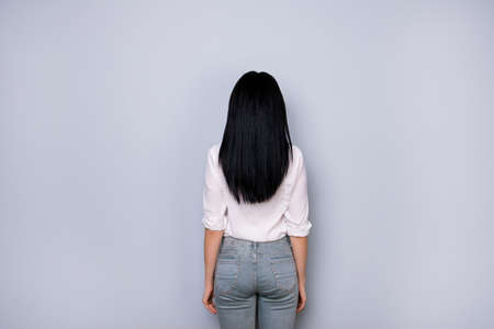 Back view of brunette lady in casual white outfit, jeans, standing still on pure light grey background