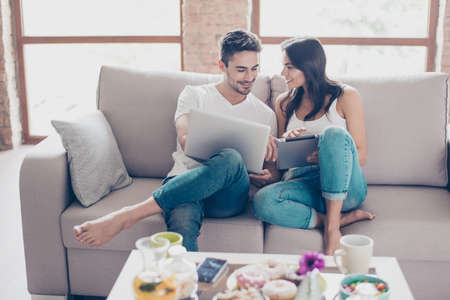 Cheerful happy couple is doing online shopping in internet at home indoors. They are on cozy beige couch in casual clothes, relaxing and buying goods easily 스톡 콘텐츠