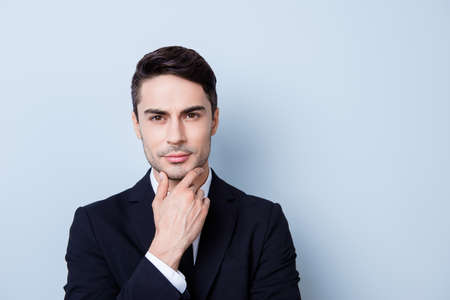 Confident pensive handsome young brunete market broker is looking straight, wearing a suit, standing on the pure background, touching his chin, being pensive and severe
