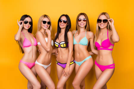 Hot brunette, blond and brown-haired girls are posing  in colorful, trendy, fashionable swimming suits and sunglasses