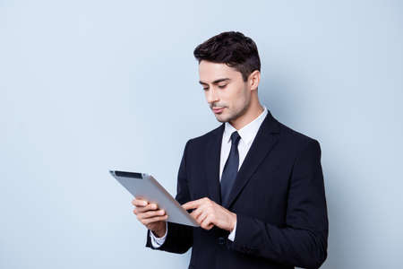pedant: Focused handsome young brunete stock-market broker is typing on his tablet, standing in a formal wear on the pure background. So serious and intelligent, successful and stylish