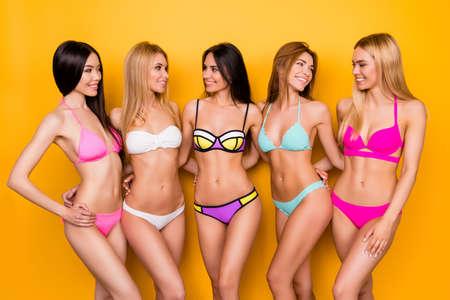 Vijf vrolijke donkerbruine, blonde en bruinharige dames genieten op vrijgezellenfeest en poseren flirterig in kleurrijke zwemkleding. Ze zijn zo warm en verleidelijk, elegant en sensueel, aantrekkelijk en gezond