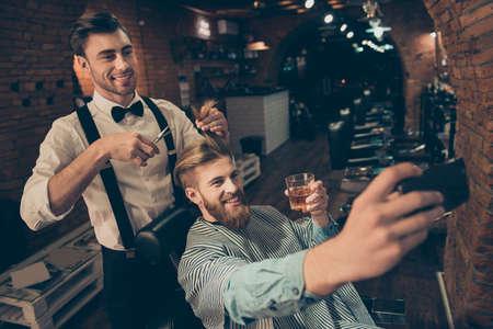 笑顔!陽気なハンサムなスタイリッシュな赤ひげを生やした男は理髪店で selfie の写真を取っている、上品な服を着て笑顔スタイリストは彼のブラン