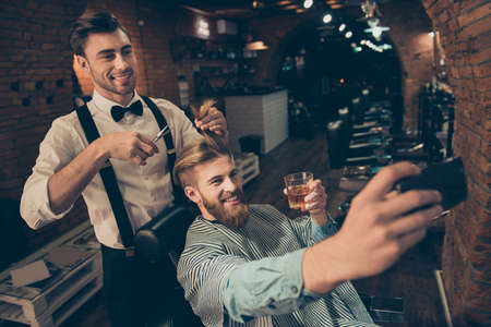 Smile! Cheerful handsome stylish red bearded guy is taking selfie photo  at barber shop, classy dressed smiling stylist is making him a brand new haircut and posing also Stock Photo