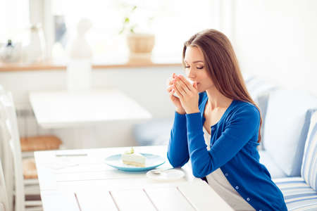 Good morning! Portrait of charming dreamy young girl drinking coffee. She is sleepy and so relaxed, in casual blue wear, in light designed restaurant Reklamní fotografie