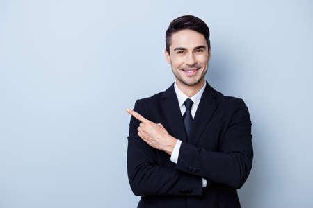 Sluit omhoog portret van jonge succesvolle brunete effectenbeursmakelaarkerel op de zuivere lichtblauwe achtergrond, glimlacht hij, draagt kostuum met band en richt op een copyspace met zijn vinger