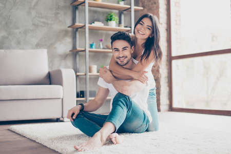 love you cheerful beautiful couple hugging at home. they are so happy, wearing casual clothes, sitting on carpet indoors at home