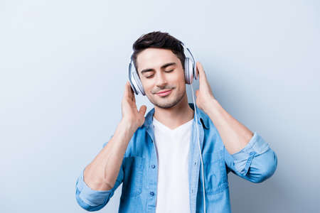 Close up portrait of cheerful young man enjoying listening to his favourite song at his holiday with closed eyes in big white earphones, wearing casual jeans outfit