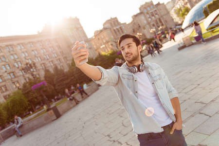 Selfie time! Young funky blogger is making photo for his social networks page, he is posing in a casual outfit and head phones, on the street in town