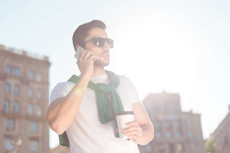 Young brunete man in a cozy outfit is talikg on the mobile, outdoors. He is on a walk outside, enjoying, holding a plastic cup of coffee in his hand