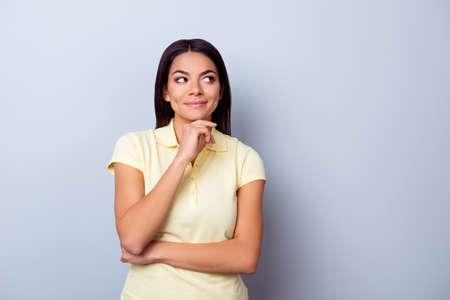Retrato de la señora joven soñadora juguetona de Brunete del americano americano, ella se coloca en camiseta amarilla en fondo ligero puro. Tan pensativo y sexy, coqueta y atractiva