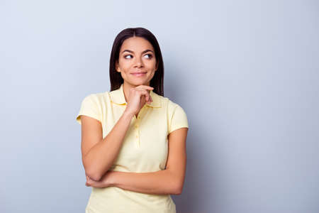 Portrait of playful dreamy young latino american brunete lady, she stands in yellow tshirt on pure light background. So pensive and sexy, flirty and attractive