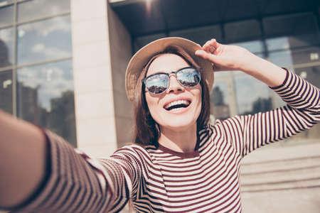Selfie マニア!興奮して若い女の子は、カメラで selfie を作っています。彼女が着ているカジュアルなストライプ春の服、サングラス、町外での散歩に 写真素材