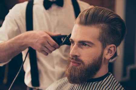 Chiuda in su di un lavoro del `s del parrucchiere per un giovane tirante bello al negozio di barbiere. Sta facendo lo styling con il rasoio elettrico Archivio Fotografico - 84622786