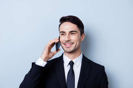 Successful and happy young brunete entrepreneur banker is having his phone nagotiations. He is in a suit and tie, standing isolated on pure background, smiling Stock Photo