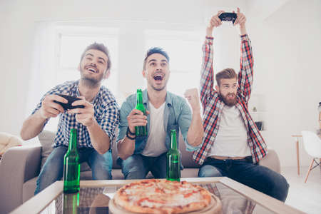 Crazy, fun, joy, winners and looser! Young men are sitting on couch and playing video games indoors at home with beer and pizza, expressing emotions and feelings, gesturing Stock Photo