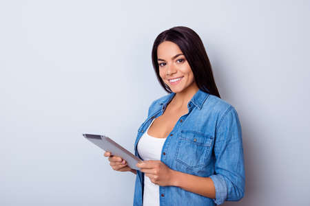 Pretty latin american brunette student is typing on her tablet, standing in a casual jeans shirt on the pure background. So attractive and intelligent Фото со стока
