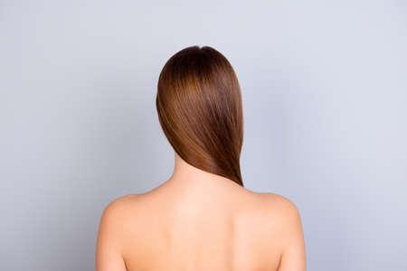 밝은 파란색 배경에 서있는 젊은 갈색 머리 소녀의 자른 된 다시보기 사진을 닫습니다. 그녀는 건강하고 빛나는 피부와 머리카락을 가지고 있습니다.