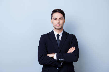 Successful young handsome brunete hispanic man lawyer in a suit on pure background with crossed hands. Severe and harsh, rich and confident, attractive and smart Stock Photo