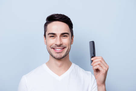 Barber shop concept. Smiling handsome young brunete in white t shirt is standing on the pure background, holds a comb in his hand. His hairdo is stylish and trendy