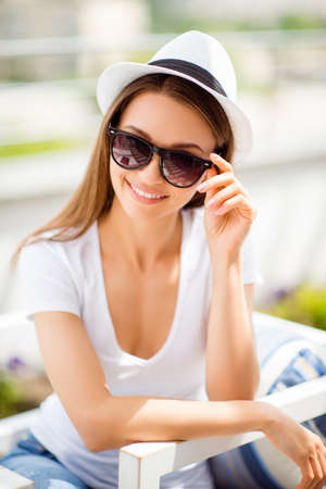Summer mood! Happy young girl on vacation in an open air light cafe. She is in a stylish hat, sunglasses and wearing casual outfit, holding her eyewear, dreamy and charming, posing
