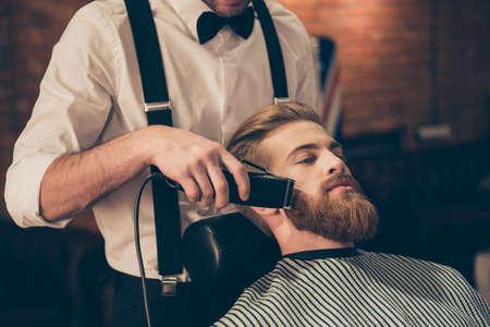 Sluit omhoog bebouwde foto van een kapper` s werk voor een knappe jonge kerel bij de kapperswinkel. Hij maakt styling met het elektrische scheerapparaat voor zijn rode baard