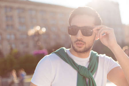 Close up of a harsh young brunete guy, walking in the city outdoors,  in casual comfortable outfit, trendy sunglasses, fixing them. He looks stylish and hot
