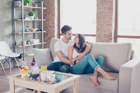 週末の朝の愛にお似合いのカップル。自宅室内でソファーにカジュアルな服装を身に着けている彼らハグします。近くには、内部テーブルにいくつ 写真素材