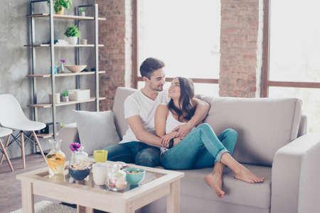 Leuk paar in liefde in de weekendochtend. Ze knuffelen binnenshuis thuis op de bank en dragen casual outfits. Er zijn enkele zoete lekkernijen aan tafel in de buurt, interieur is modern en gezellig