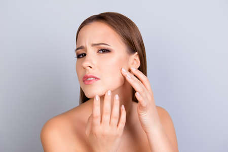 Perfection is a hard work. Acne, pimple, clear and clean, oily, dry  skin concept. Cose up cropped photo of worried young lady touching her face gently Stock Photo - 84608080