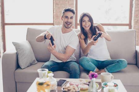 誰が勝つだろうか。車のレースを再生兄弟の競争。興奮して友人が自宅室内でのゲームをプレイ、居心地の良いベージュのソファに座って、自分自 写真素材